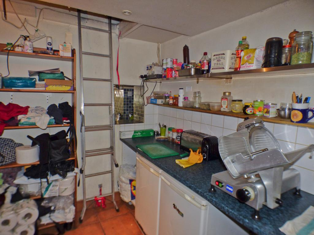 Kitchen with access to suspended storage area
