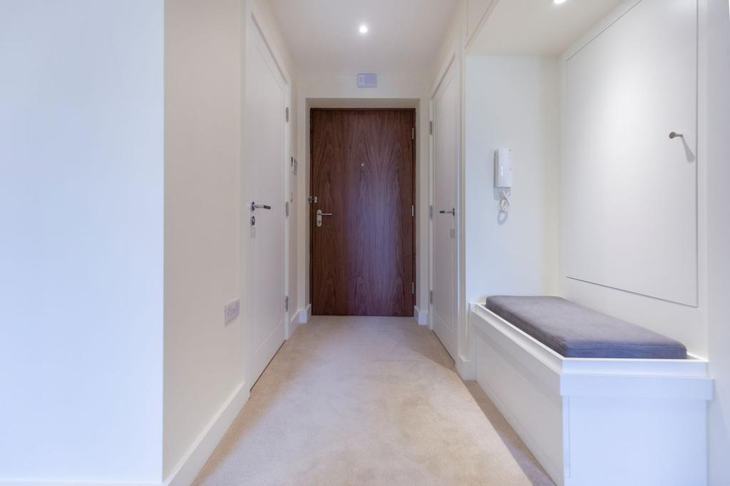 Entrance hallway with feature wallpaper, wall lights and a handy storage seat