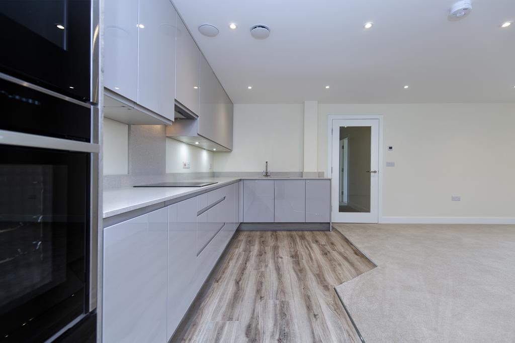 Spacious living kitchen with french doors to a balcony with glass balustrading