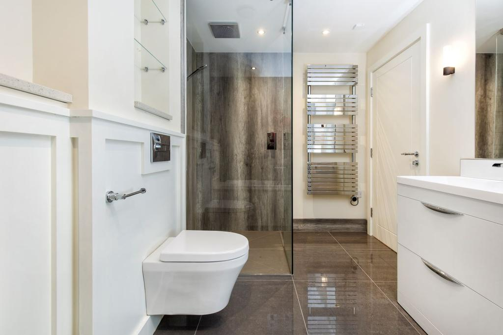 Large shower cubicle enclosed with a light marble effect waterproof panelling and floor to ceiling glass