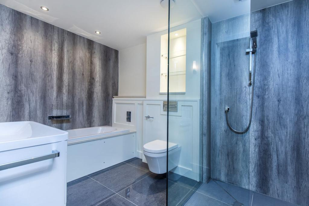 Bathroom with decorative wood panelling and dark marble splash walls to the shower and fitted bath